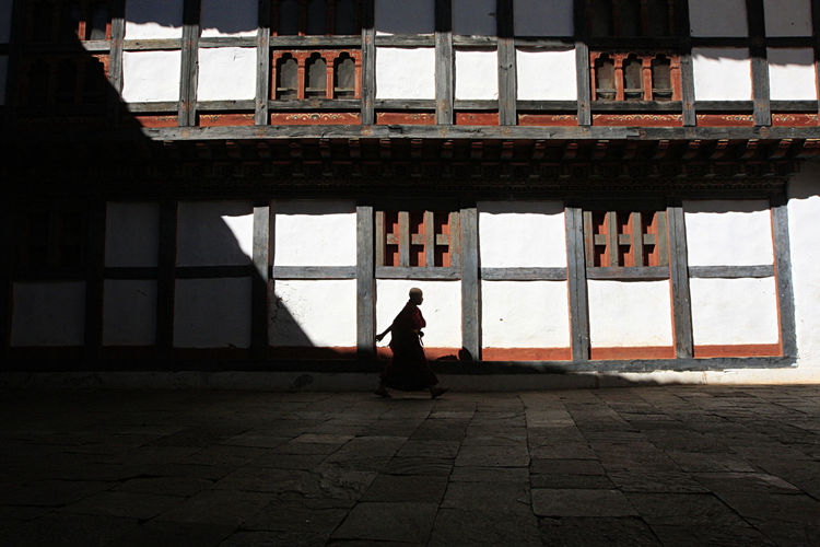 Silhouette woman sitting on window of building