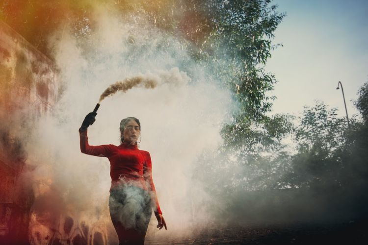 Low angle view of woman holding distress flare against trees