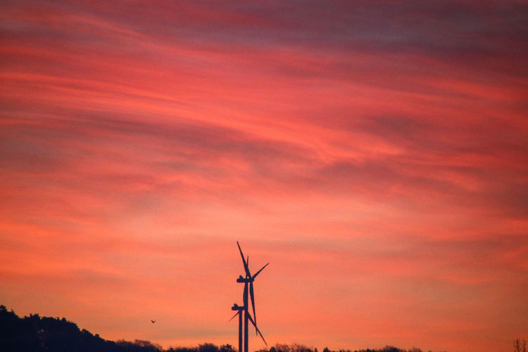 Low angle view of silhouette wind turbine against orange sky