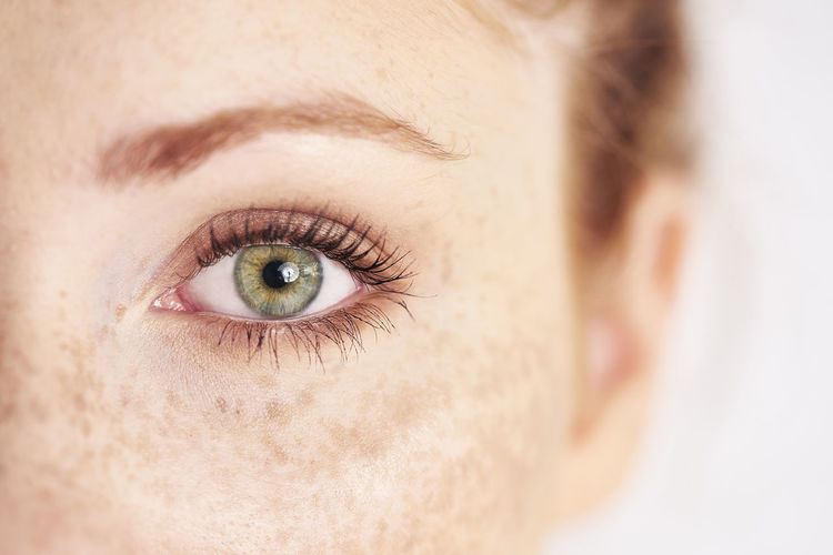 Cropped eye of woman against white background