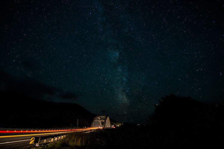 Light trails on ten mile creek bridge against sky at night