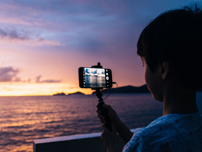 Close-up of man holding camera while standing by sea against sky