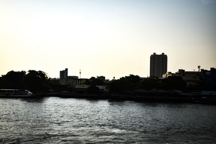River and buildings against sky during sunset