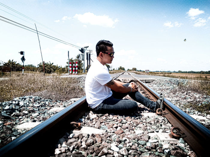 Side view of young man sitting on railroad track
