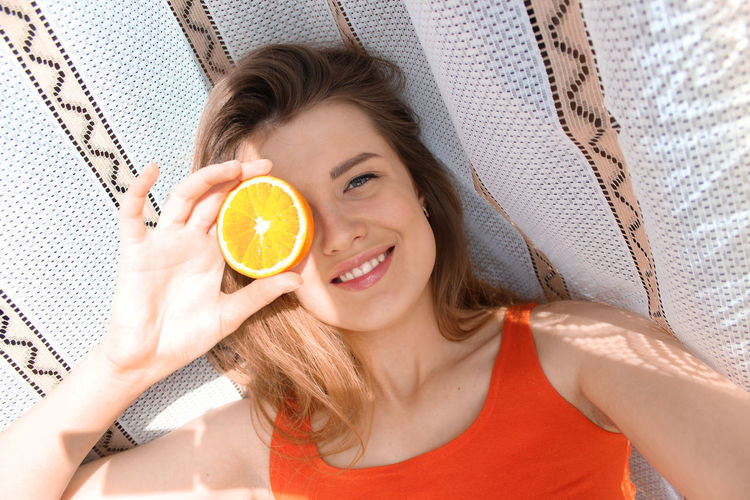 High angle portrait of happy woman holding fruit while lying on hammock
