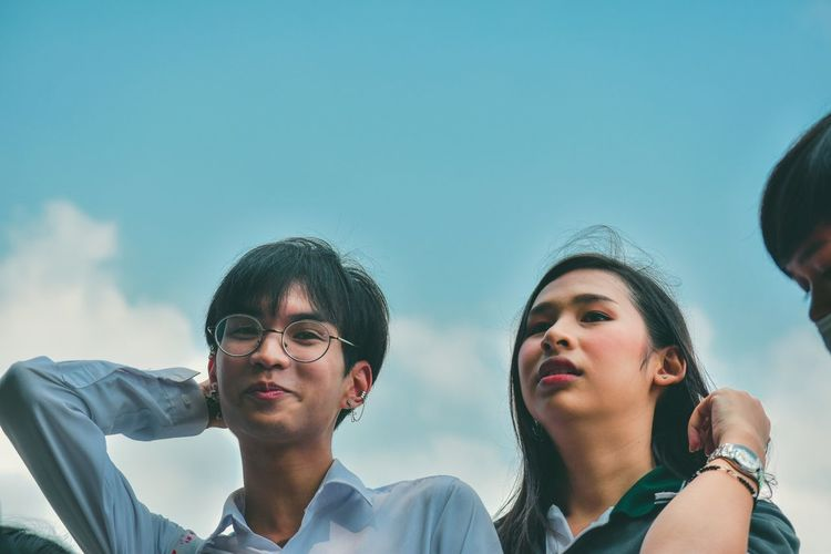 Low angle view portrait of friends standing against sky