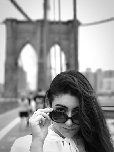 Portrait Of Young Woman Holding Sunglasses On Bridge