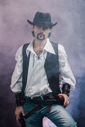 Handsome young man. This is an American cowboy. A vow to a white shirt, brown waistcoat and blue jeans. Black shoes on the feet. Carries a shtyapa, on a belt two pistols. The hair is of medium length; on the face is a beard and mustache. Authentic photo. Culture of America. Cowboy Wild West America American Gun National Authentic Moments Lifestyles Lifestyle One Person Candid Authentic Three Quarter Length Front View Real People Clothing Men Beard Hat Young Adult Young Men Males  Adult Mid Adult Standing