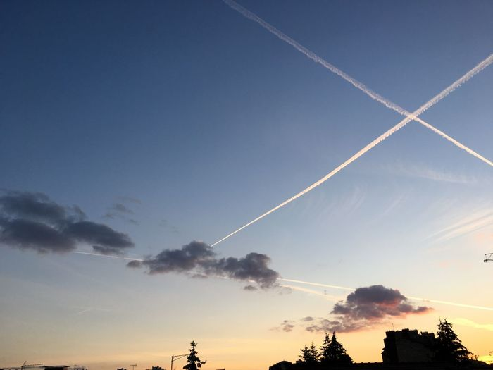 Low angle view of vapor trails in sky at sunset