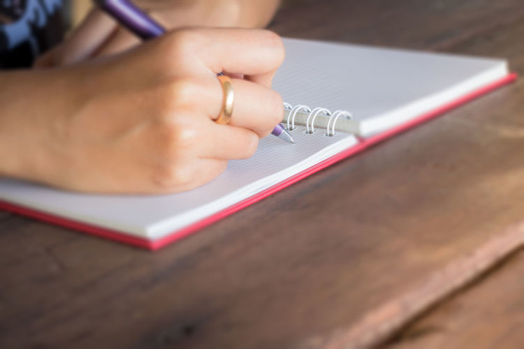 Close-up of woman writing in note book