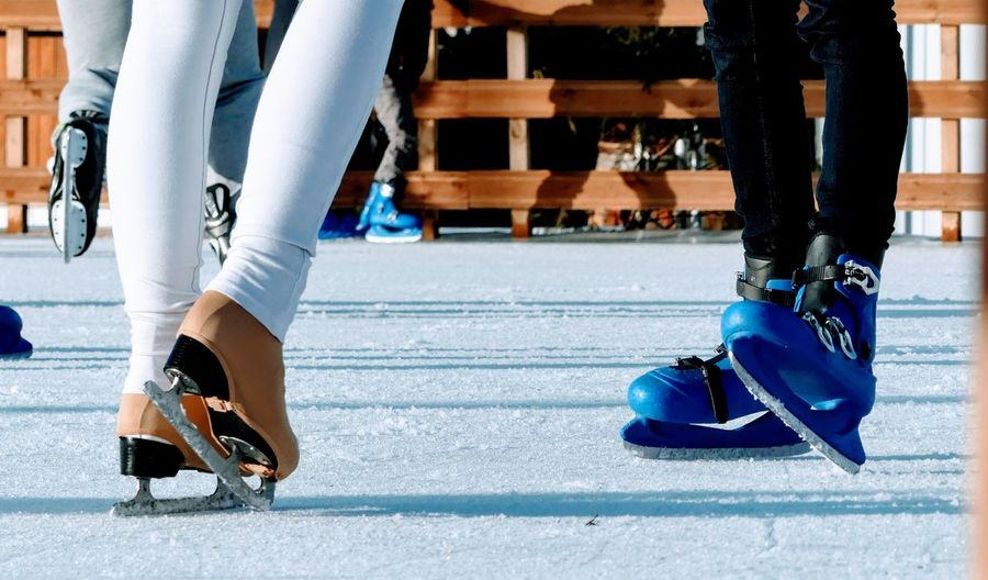 Low section of people ice-skating on rink