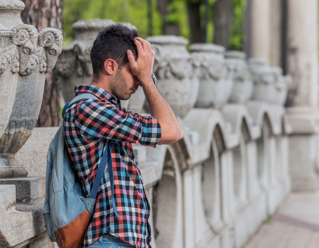 Side view of tired young man rubbing eyes while standing on footpath