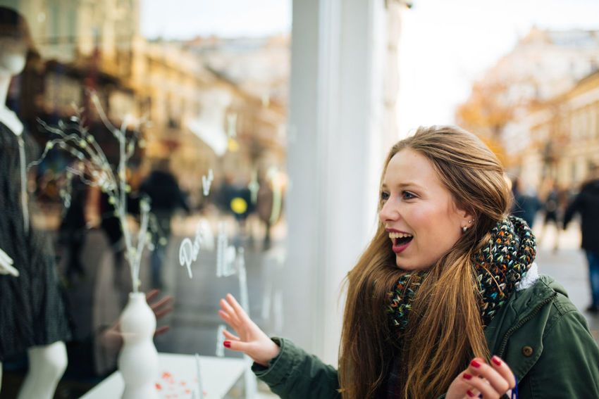 Attractive young long haired woman is excited in front of shopping window Boutique Business Sale Santas Hat Shopping Standing Window Shopping Buying Consumerism Customer  Emotion Gift Hair Happiness Leisure Activity Real People Retail  Shopaholic Shopping Bag Shopping Mall Smiling Store Store Window Street Window