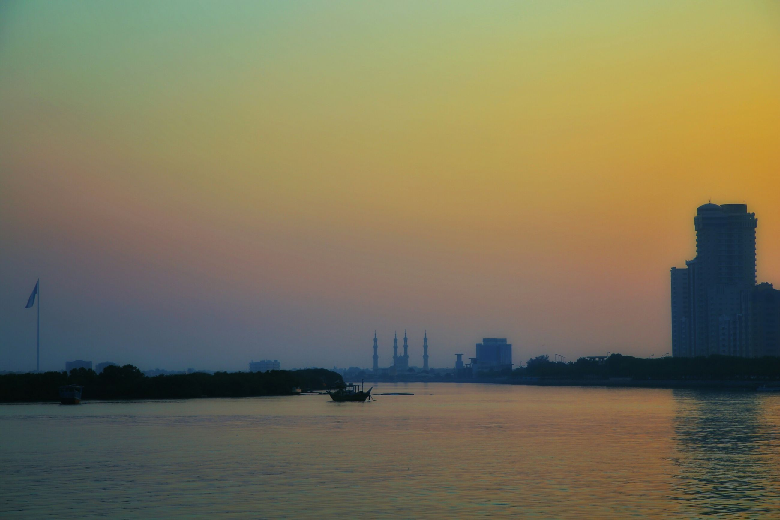sunset, waterfront, water, building exterior, architecture, built structure, orange color, sea, copy space, scenics, silhouette, city, nautical vessel, transportation, beauty in nature, river, clear sky, sky, nature, tranquility