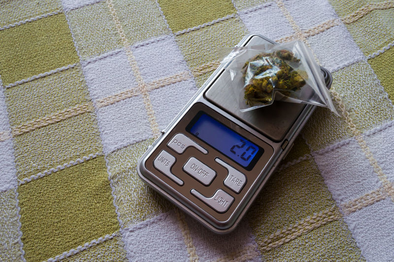 High angle view of marijuana with weight scale on table