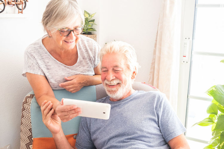 Pretty senior couple smiling and looking together the same phone. Bright background with natural plants. Two caucasian people Activity Adult Armchair Arms Background Beard Bright Casual Caucasian Cellular Day Decoration Elderly Enjoying Eyeglasses  Friendship Front View Hands Home Indoor Lifestyle Light Looking Love Married Mobile Phone Natural Old Pensioner People Plants Relax Retired Retirement Senior Sharing  Smiling Sunlight Talking Technology Telephone Together Touching Two Person White White Hair Window Wireless Wood Senior Adult