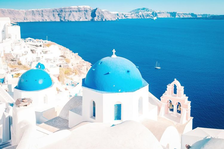 Panoramic view of sea and buildings against blue sky, santorini greece