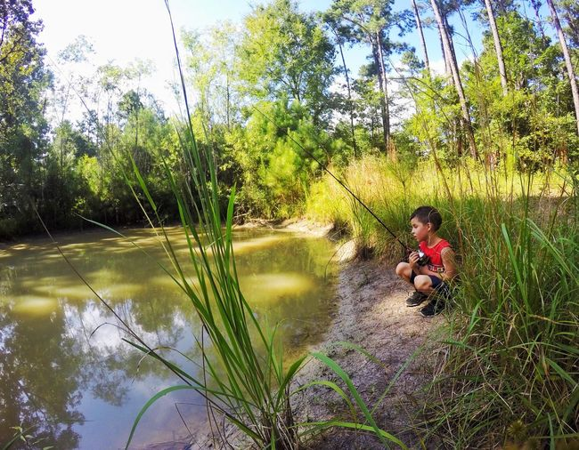 Boy fishing in river while crouching at riverbank