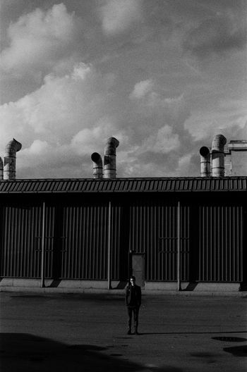 a man standing in an industrial zone Focus On Foreground Portrait Blackandwhite Outdoors Lifestyles Moody EyeEm Best Shots EyeEmNewHere EyeEm Selects Clothing Portrait Photography Film Photography 35mm Film Ilford Streetphotography Street Outdoor Photography Analog Film Industrial Lifestyles Prison Standing Full Length Sky Architecture Building Exterior Built Structure Prisoner Cobblestone