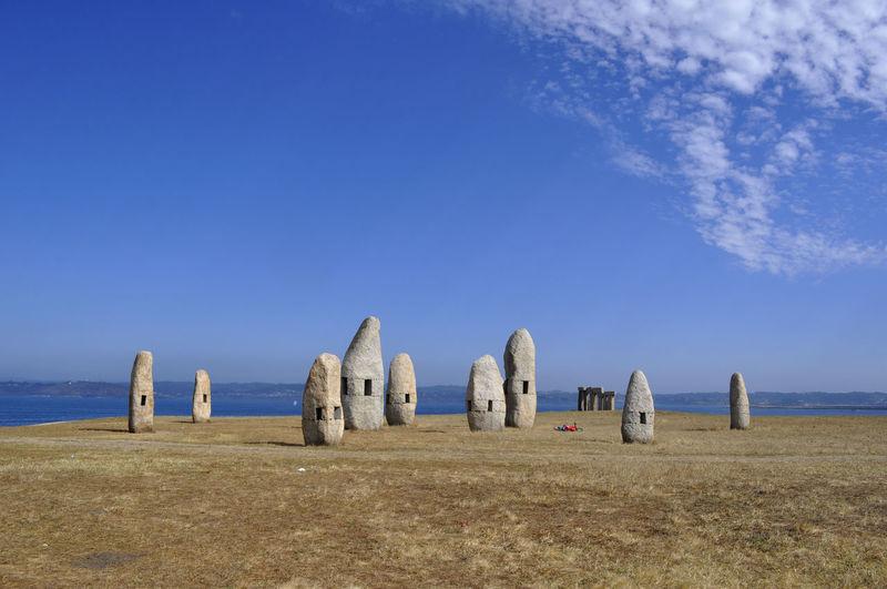 Hay bales on landscape against blue sky
