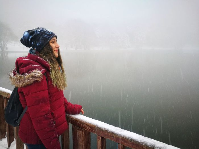Woman standing by lake during winter