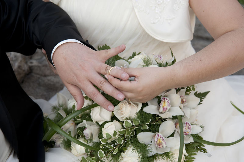 Cropped image of bride placing ring on groom in wedding ceremony