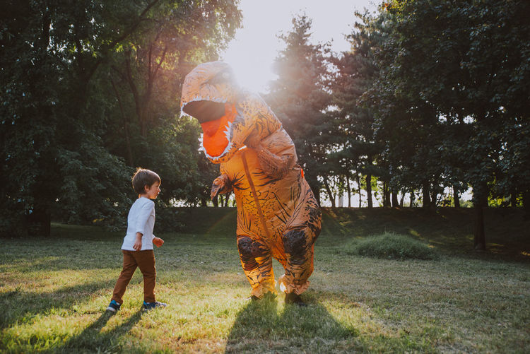 Boy playing with person wearing dinosaur costume in park