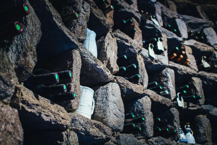 Full frame shot of wine bottles in stone wall