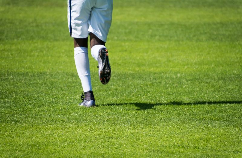 Low section of soccer player running on field