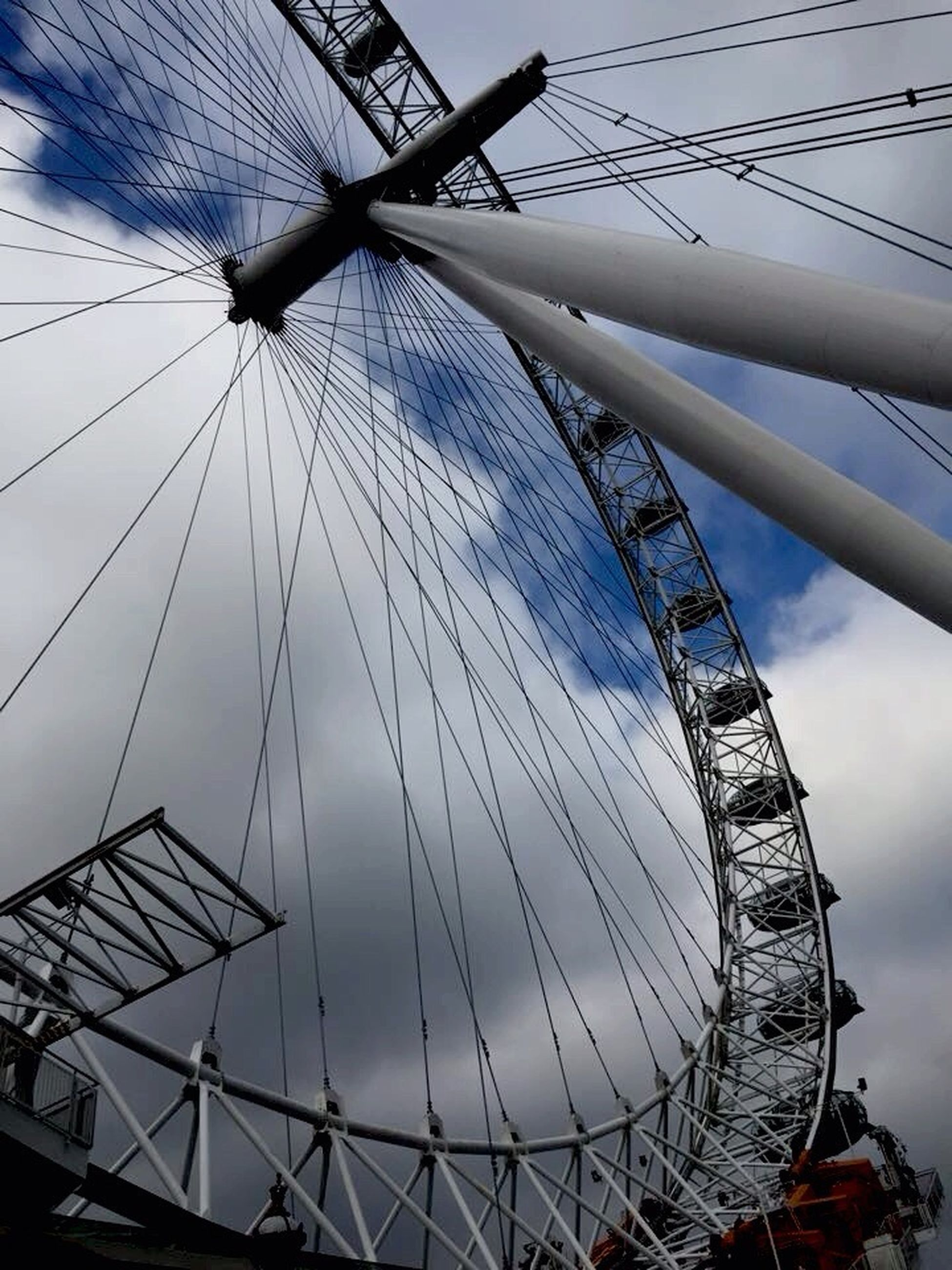 low angle view, ferris wheel, sky, amusement park ride, amusement park, transportation, metal, arts culture and entertainment, mode of transport, built structure, part of, cloud - sky, metallic, engineering, day, architecture, connection, outdoors, travel, no people
