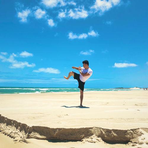 Full length of man exercising on beach against sky