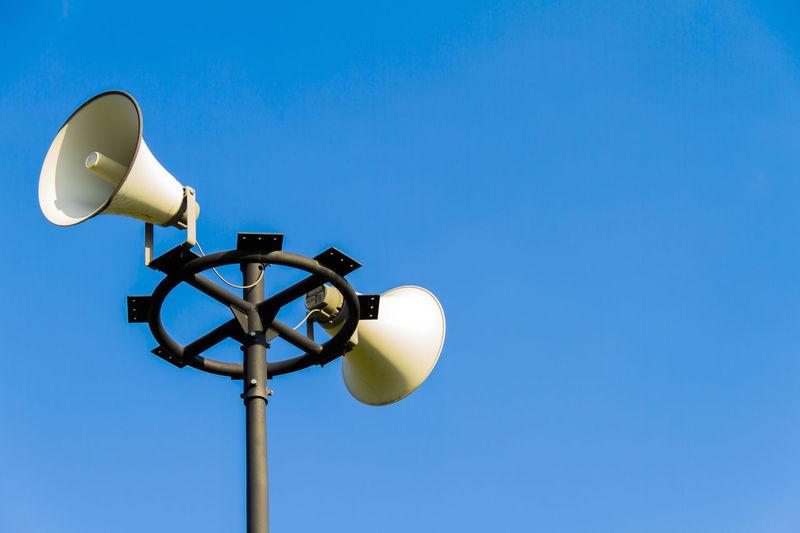 Low angle view of megaphones against clear blue sky