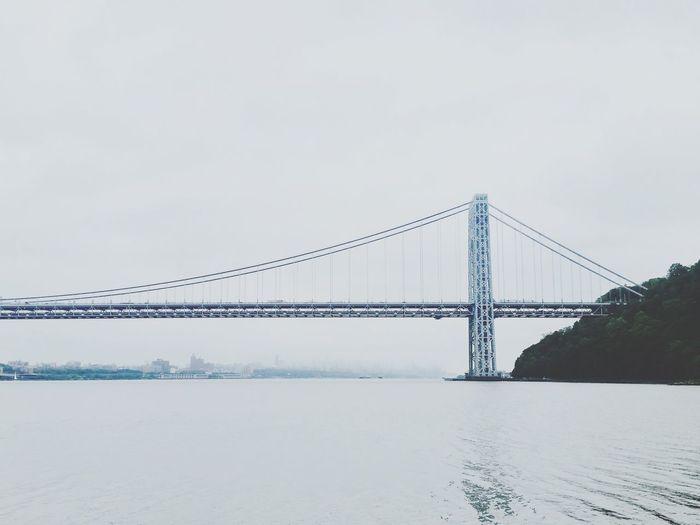 View of suspension bridge over calm sea