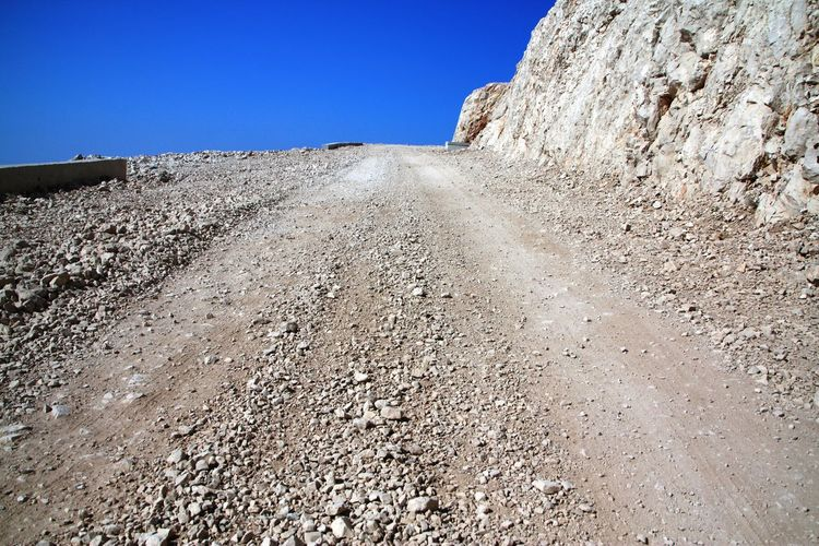 Macadam road going up, blends with clear blue sky Clear Sky Day Diminishing Perspective Direction Dirt Dirt Road Environment Gravel Land Landscape Macadam Nature No People Outdoors Quarry Road Rock Rock - Object Sky Solid Surface Level The Way Forward Transportation