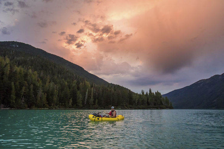 People on boat in lake against sky during sunset