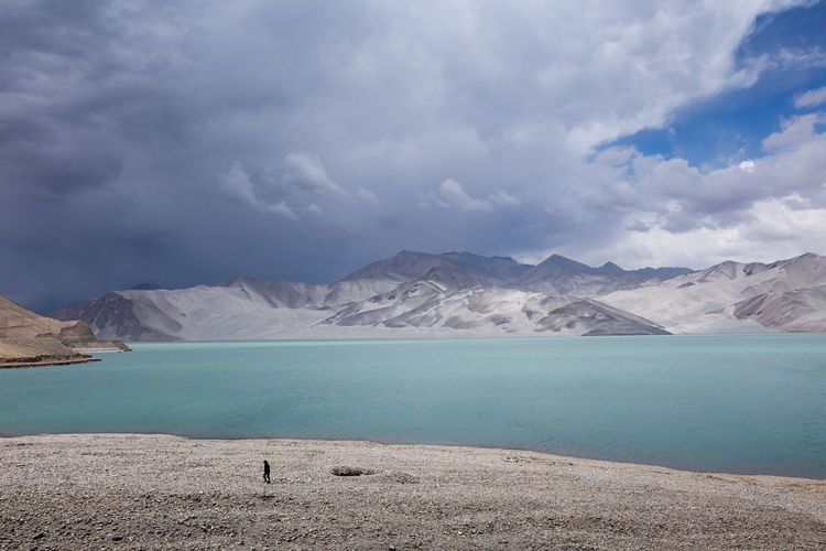 A surreal looking lake along the Karakoram highway Beauty In Nature Cloud - Sky Dune Lake Lakeshore Nature Solitary Man Tranquility Travel Water