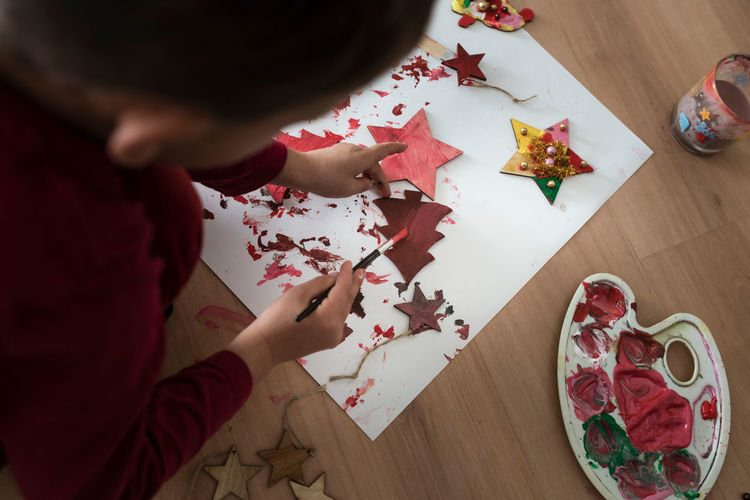 High angle view of boy playing with paper on table