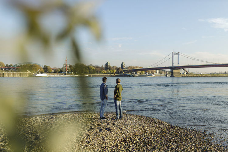 People standing on suspension bridge over sea against sky