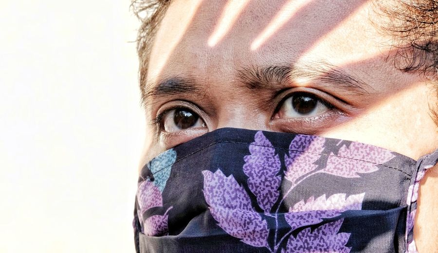 Close-up portrait of man covering face against white background