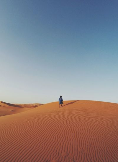Man Walking In Desert Against Clear Blue Sky