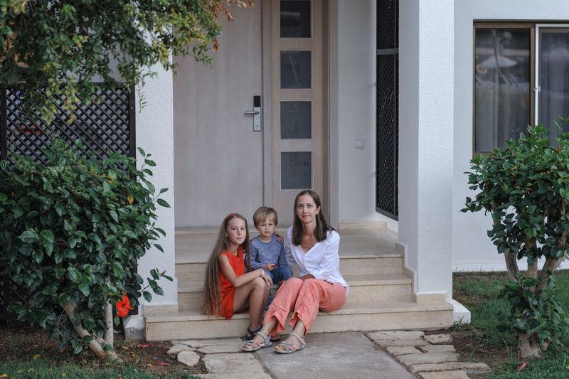 Portrait of family sitting on steps against house
