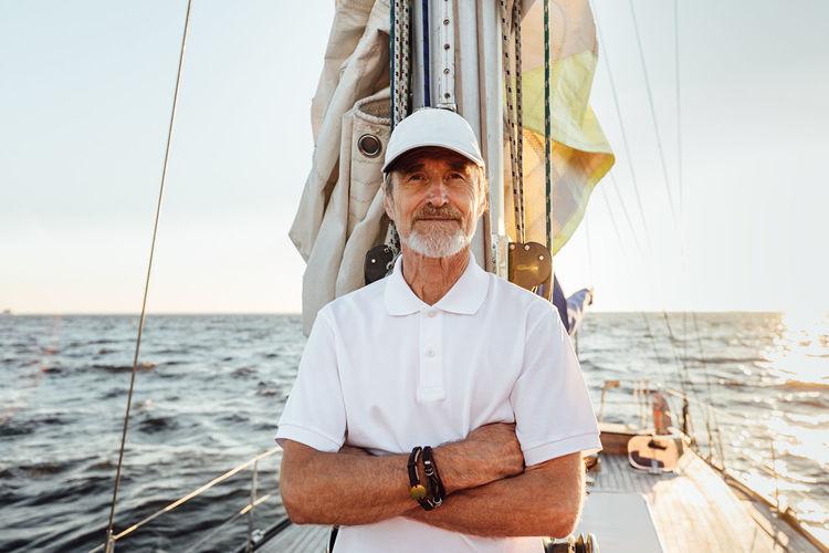 Portrait of senior man at sea against sky