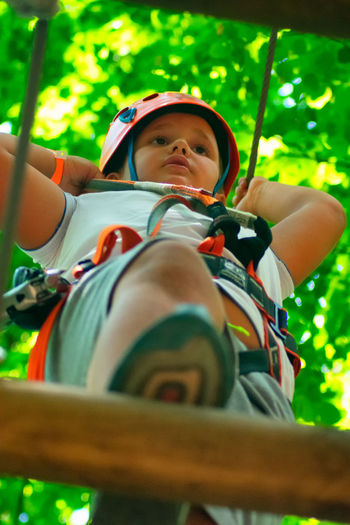 Cute boy sitting on zip line in forest
