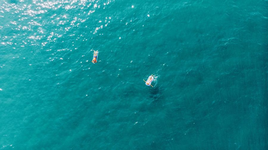Aerial View Of Man And Woman On Inflatable Raft In Sea