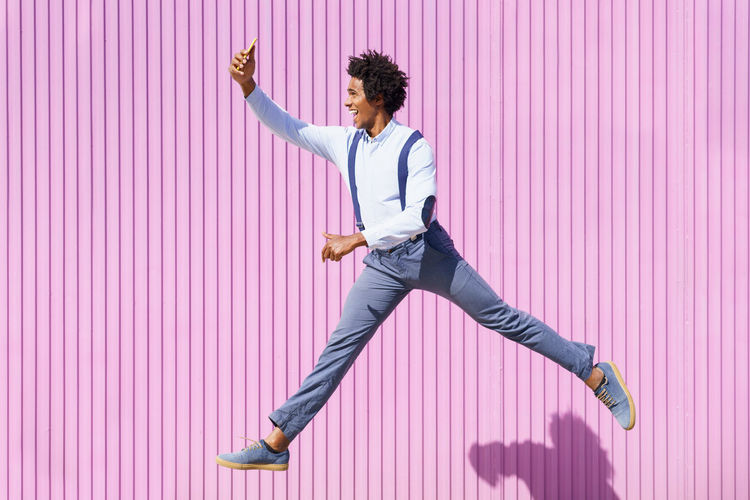Full length of man with arms raised standing against pink wall