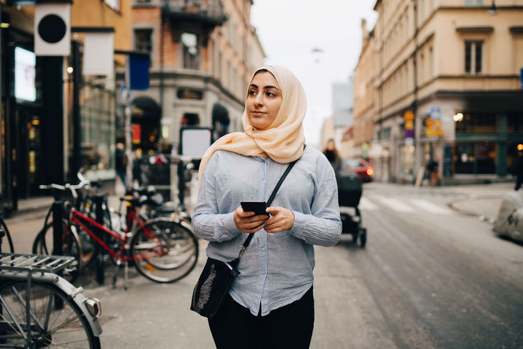 Young woman using phone while standing on city street