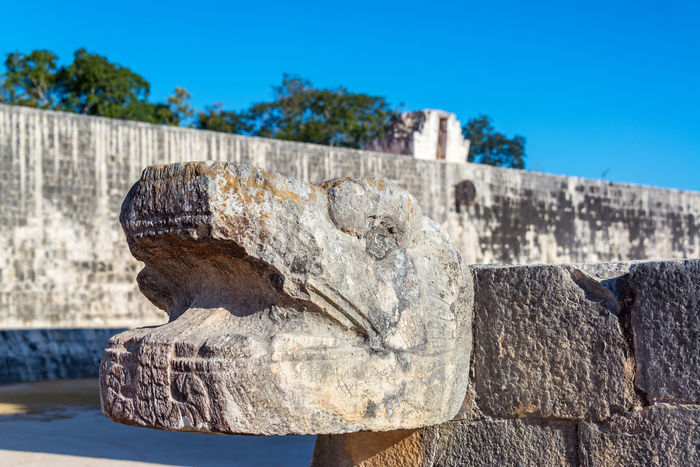 Snake head with the ball court in the background in the ancient Mayan ruins of Chichen Itza in Mexico Ancient Archeology Architecture Cancun Chichen Chichen Itza Chichenitza City Civilization Landmark Maya Mayan Mexican Mexico Old Pyramid Sacred Site Stone Temple Tourism Travel Unesco World Yúcatan