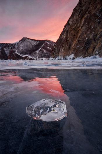 Frozen lake against mountain during sunset