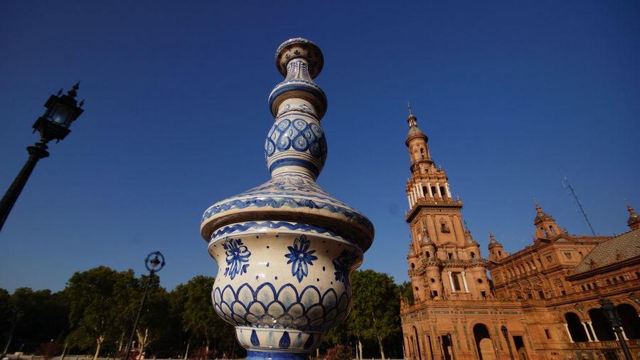 Low angle view of porcelain sculpture at plaza de espana against clear sky