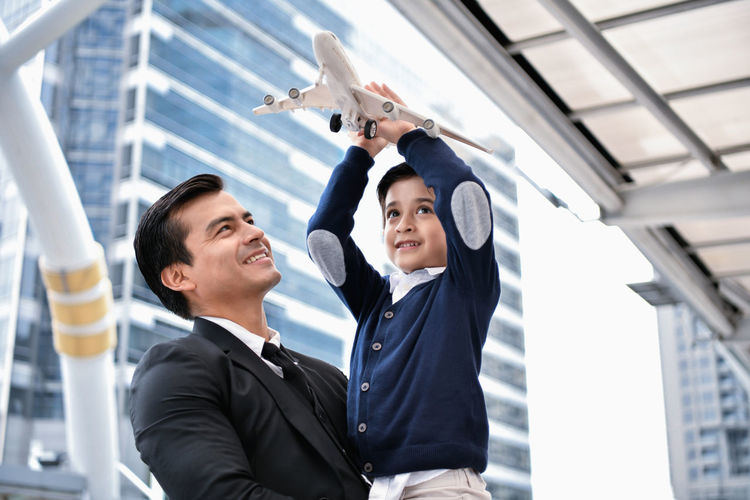 Smiling father carrying son with model airplane